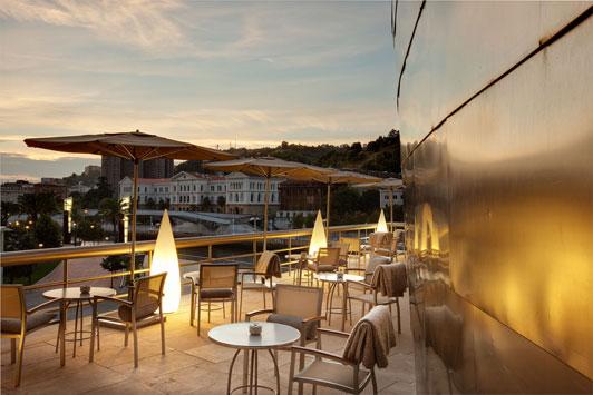 Una terraza de Bistró Guggenheim Bilbao, un espacio exclusivo rodeado de titanio, disfruta de nuestra carta de cócteles en un entorno único en el mundo